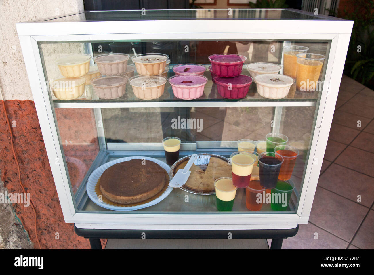array of delicious delicately colored gelatin desserts in display case in open doorway on street Oaxaca Mexico - Stock Image