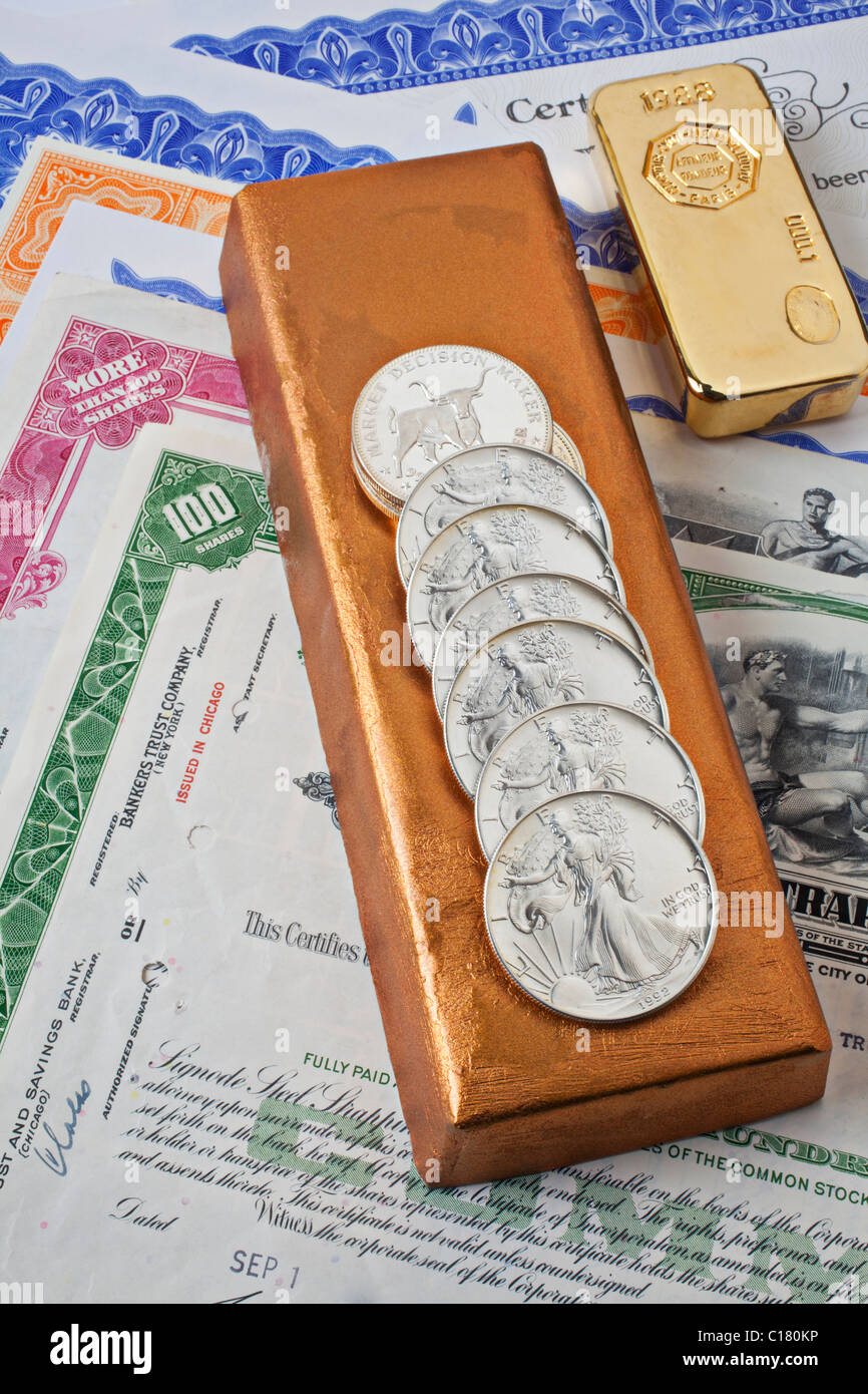Silver coins and gold bars - Stock Image