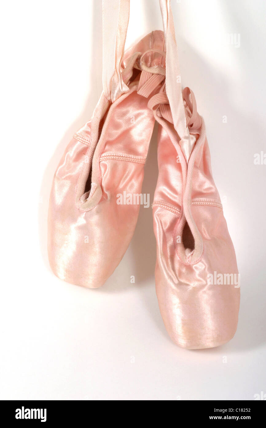 A pair of new, once worn, ballet shoes or toeshoes hanging on the wall. - Stock Image