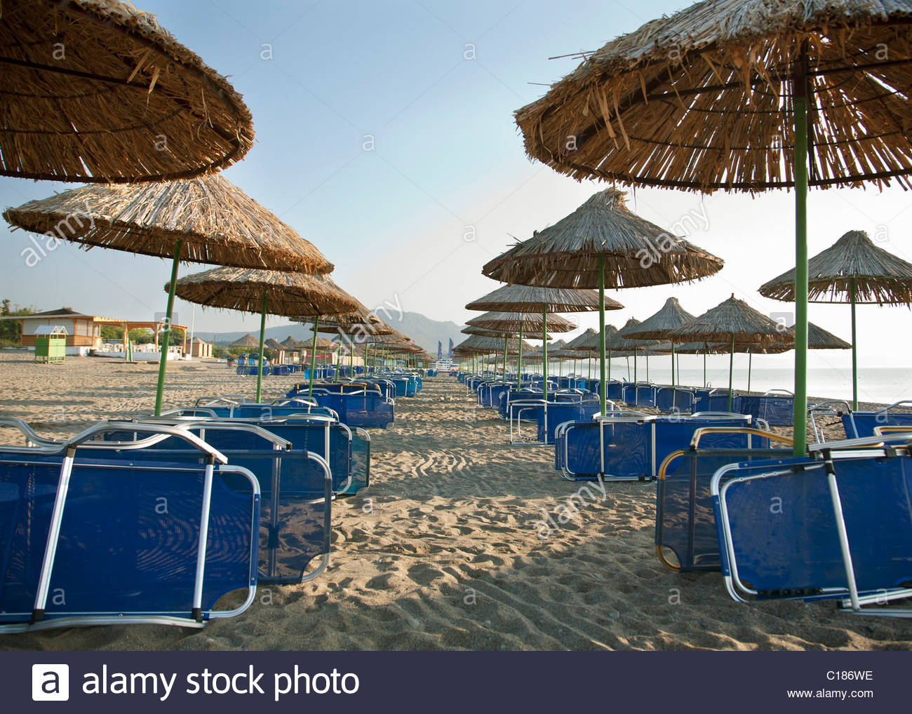 Parasols and sun loungers on beach - Stock Image