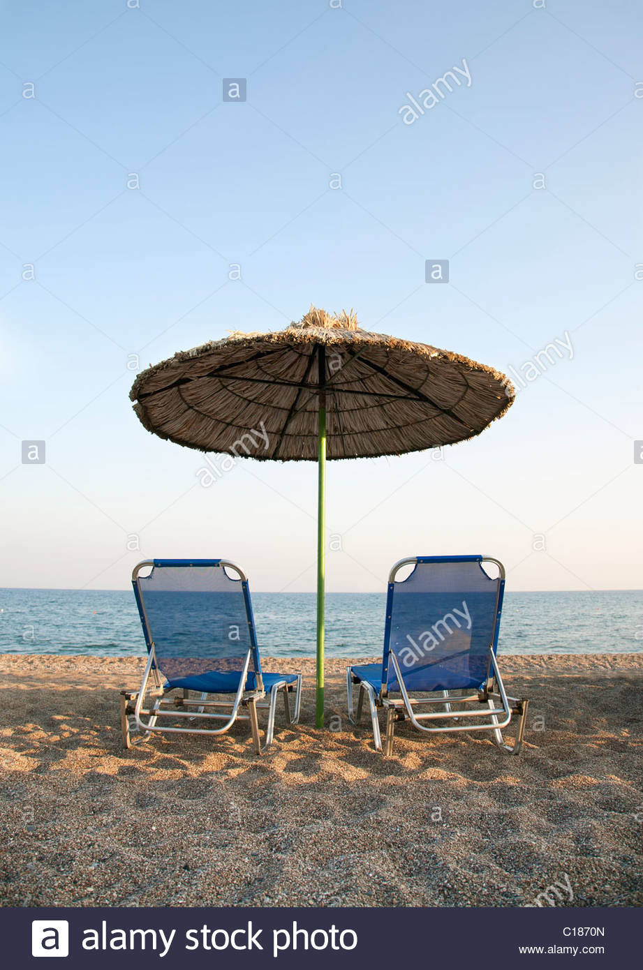 Two sun loungers and parasol on the beach - Stock Image