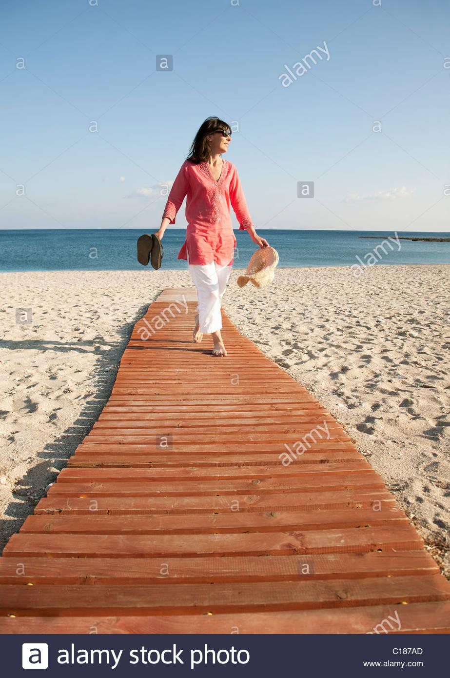Woman walking on boardwalk on beach Stock Photo