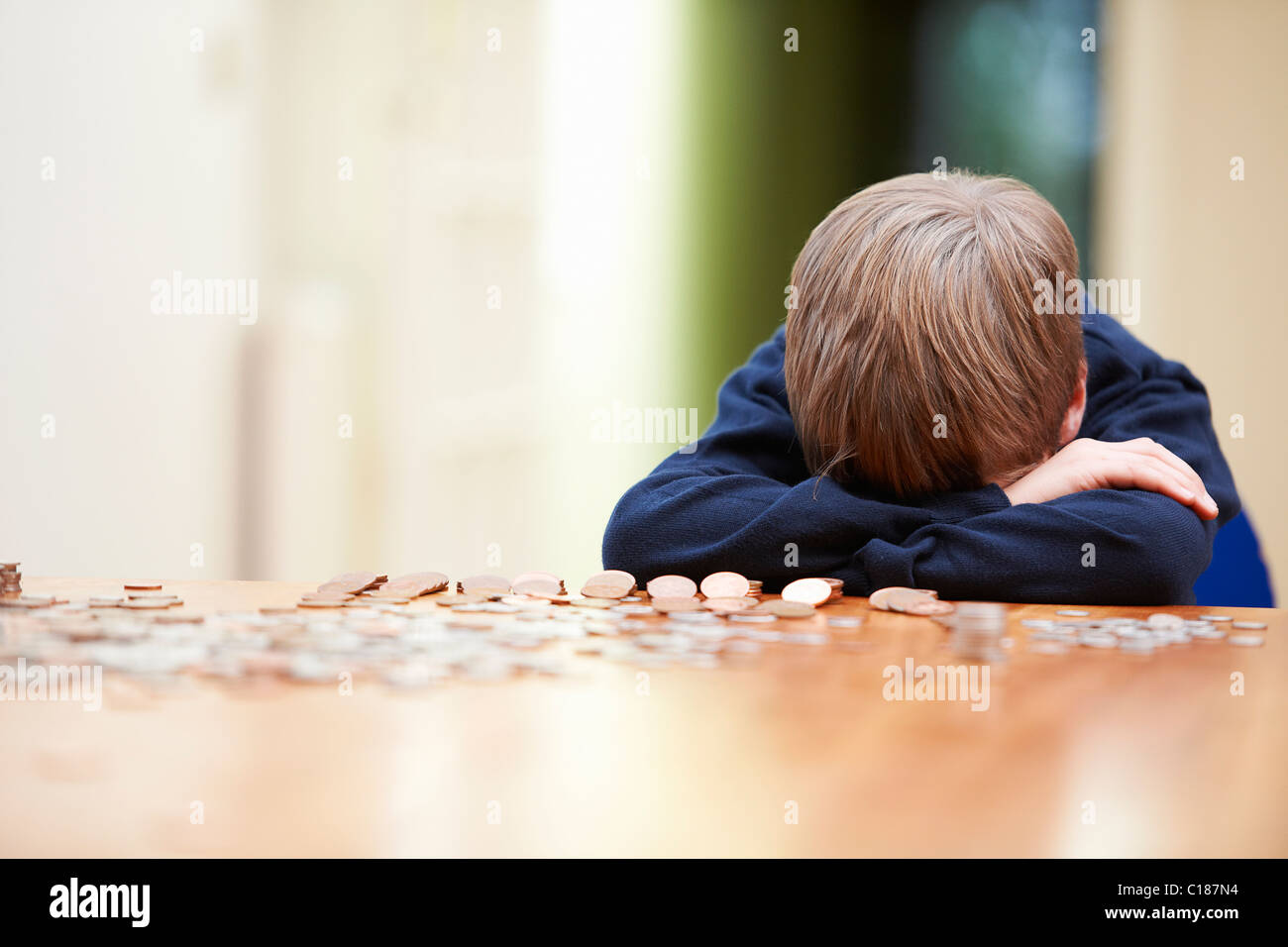 Boy head on arms surrounded by coins - Stock Image