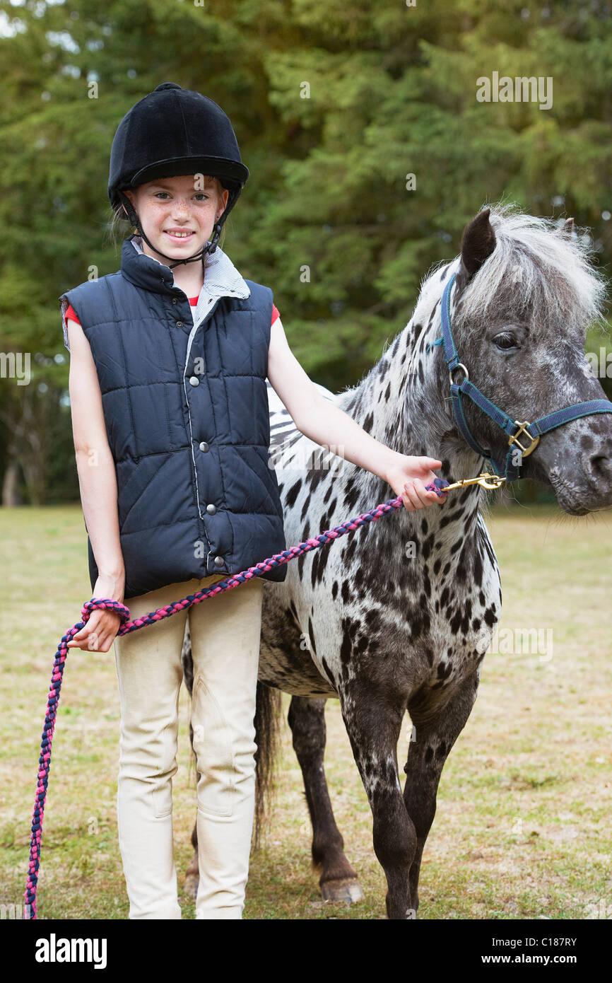 Girl standing with horse - Stock Image