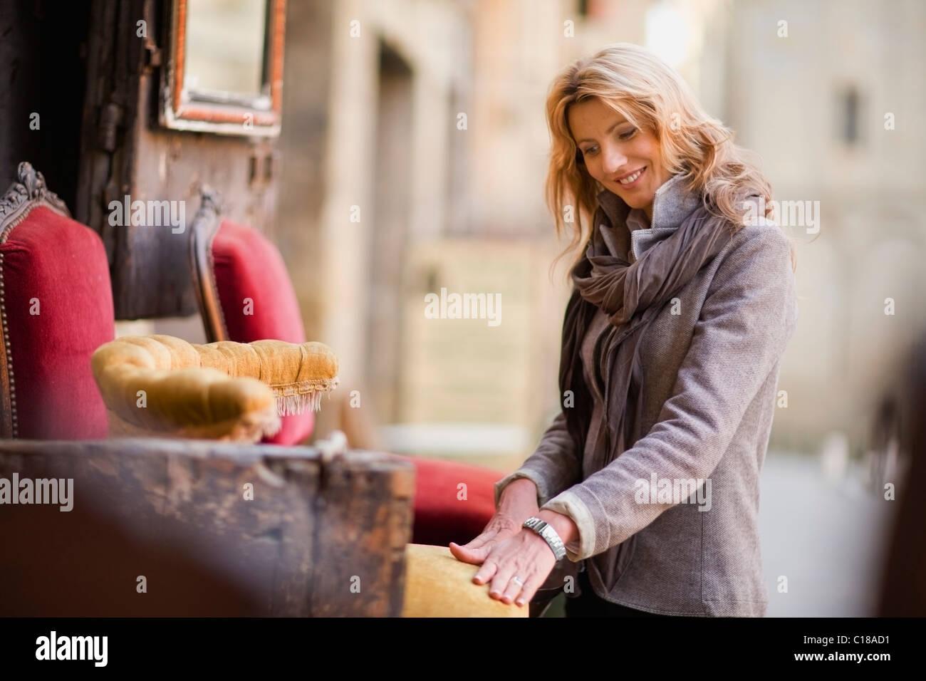 Woman marveling at antique furniture - Stock Image