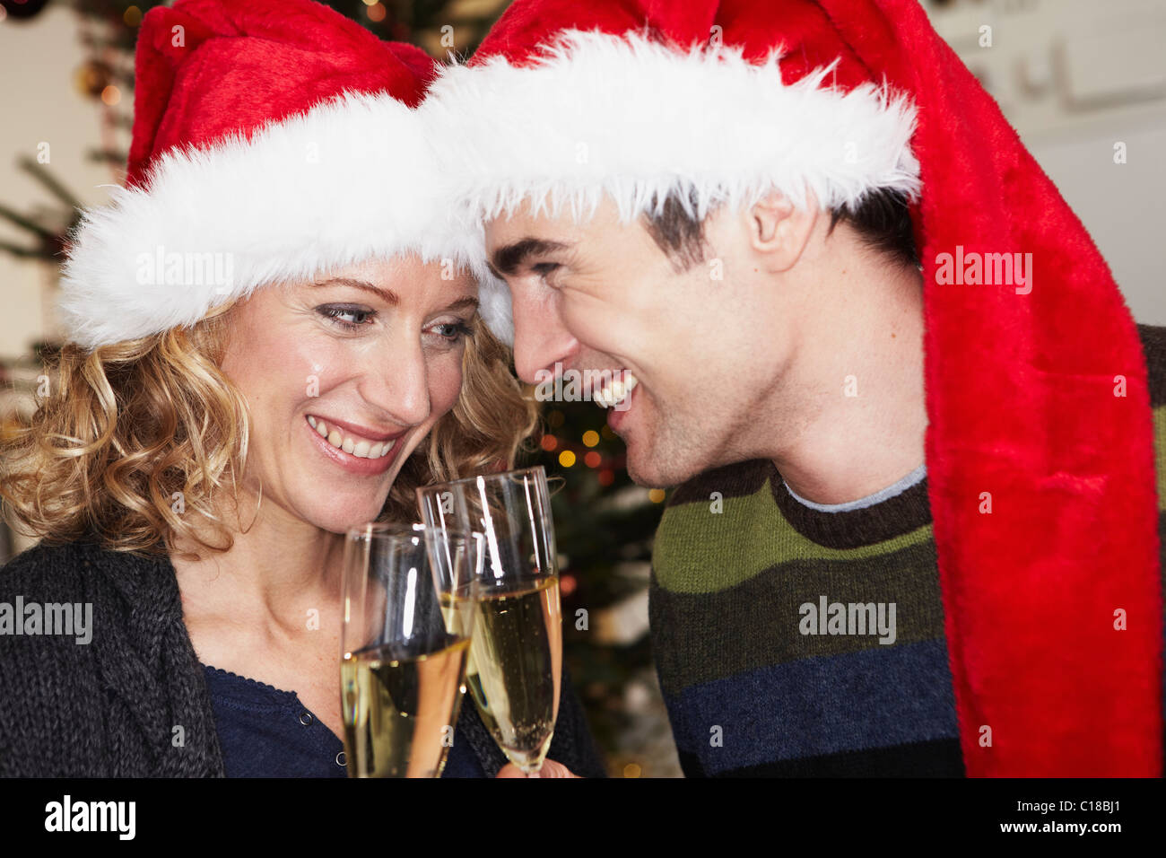 Couple with xmas caps clinking glasses - Stock Image