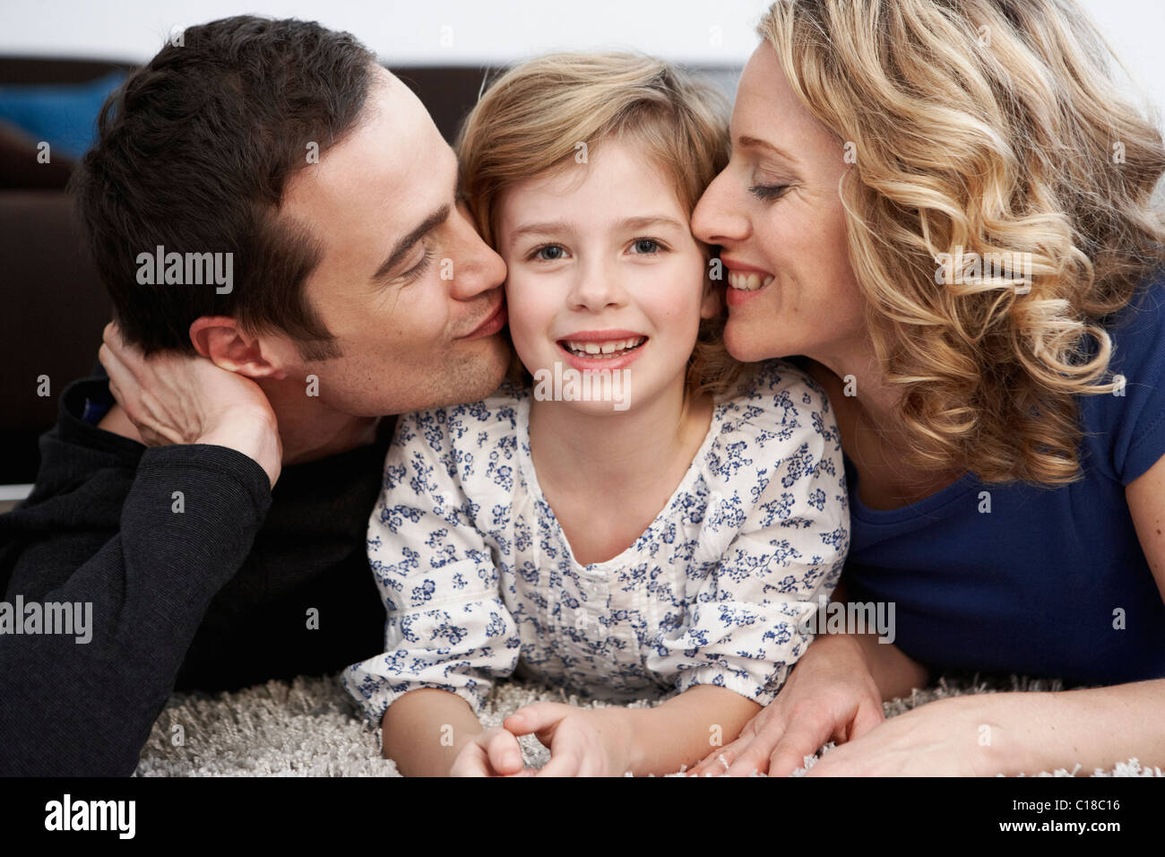 Parents kissing daughter on cheeks - Stock Image