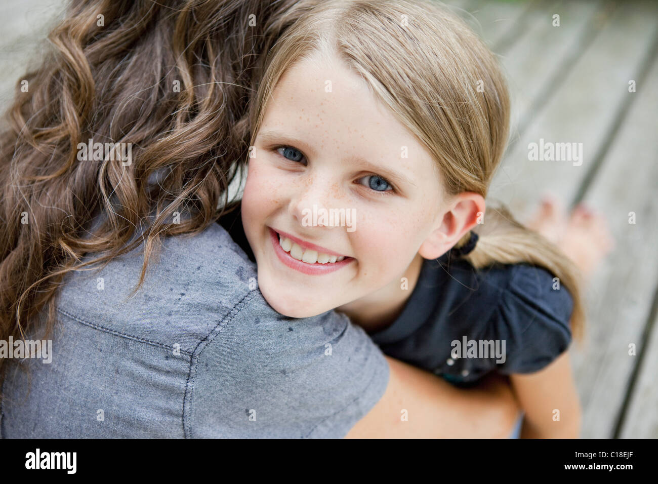 Girl happily hugging her mother - Stock Image