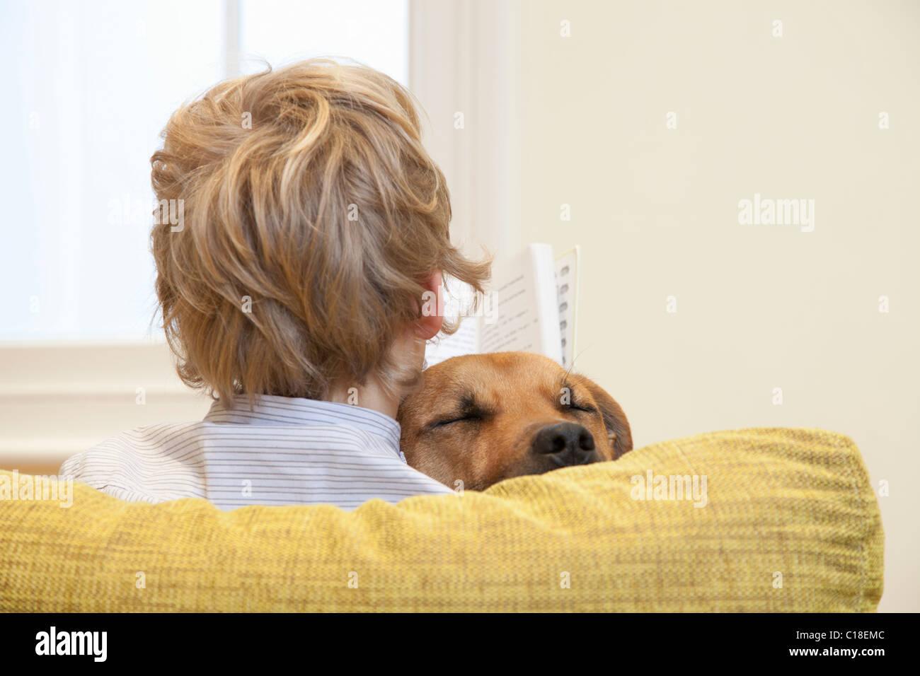 Boy reading whilst cuddling dog - Stock Image