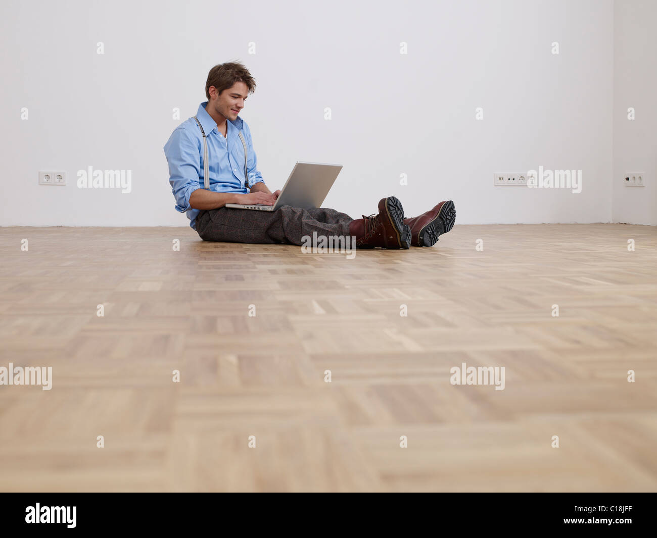 Young man with laptop in empty flat - Stock Image