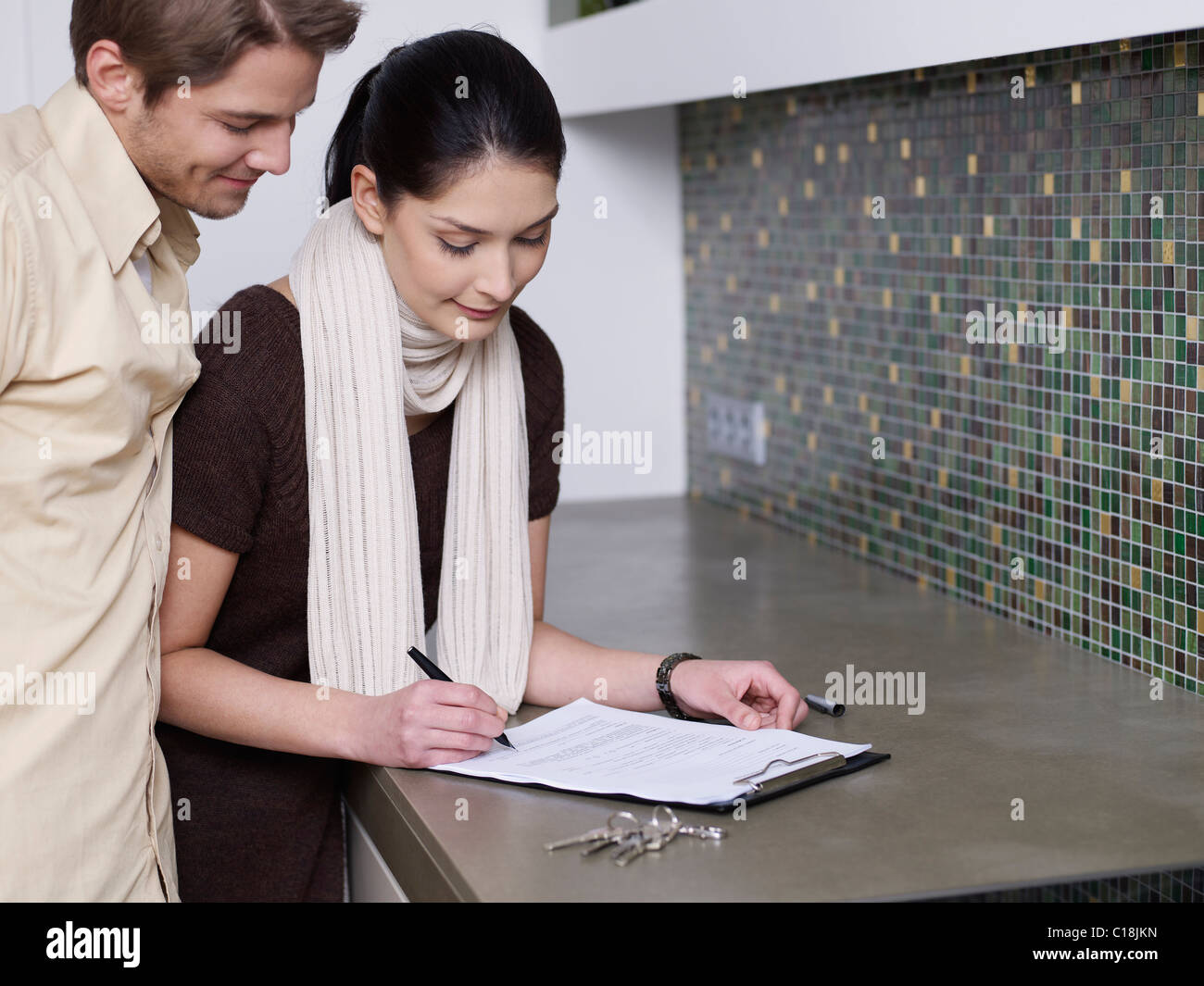 Couple signs tenancy agreement - Stock Image