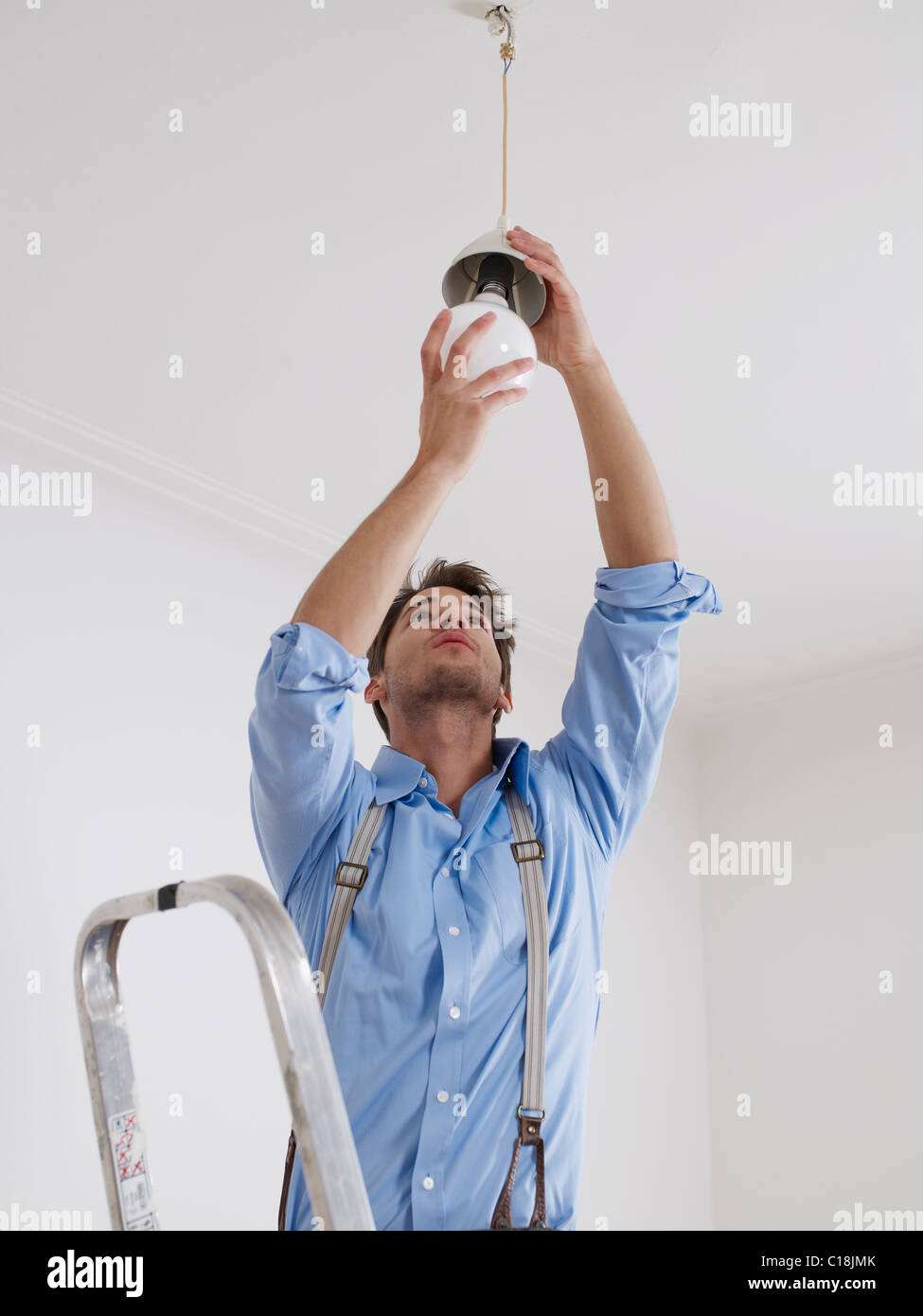 Changing Light Bulb Stock Photos Images Wiring A Young Man On Ladder Screws In Image
