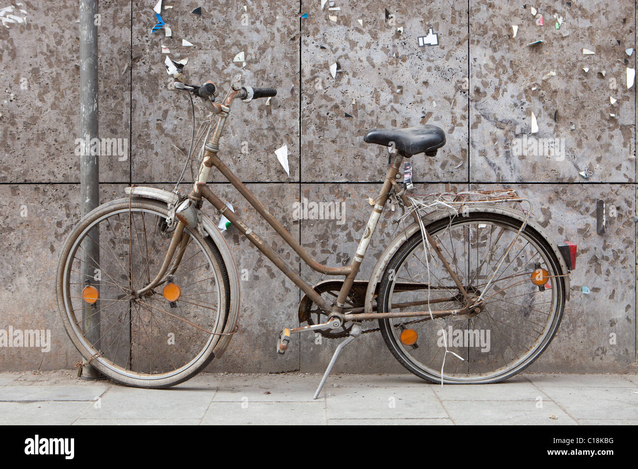 Old bike in front of a weathered wall - Stock Image