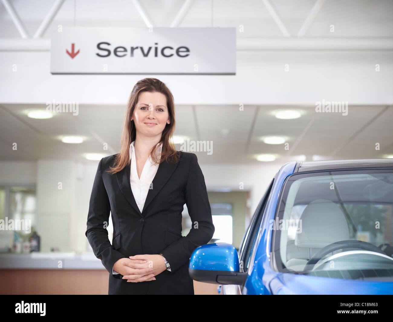 Saleswoman with car in car dealership - Stock Image