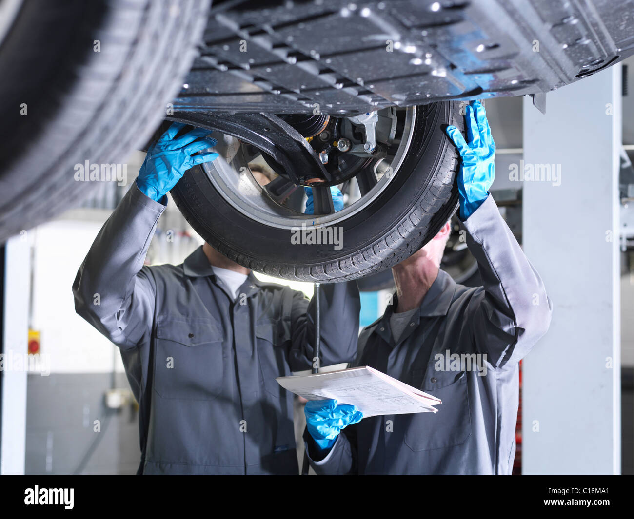 Mechanics working under car - Stock Image