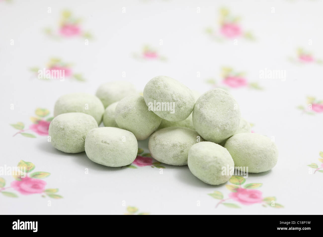 apple bonbons sweets and candy on a paper background photographed in a studio - Stock Image