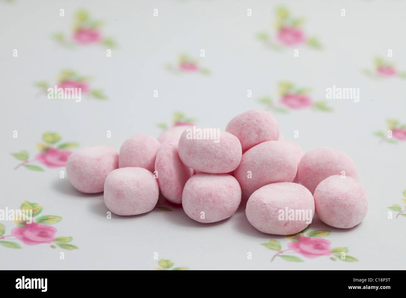 cherry bonbons sweets and candy on a paper background photographed in a studio - Stock Image