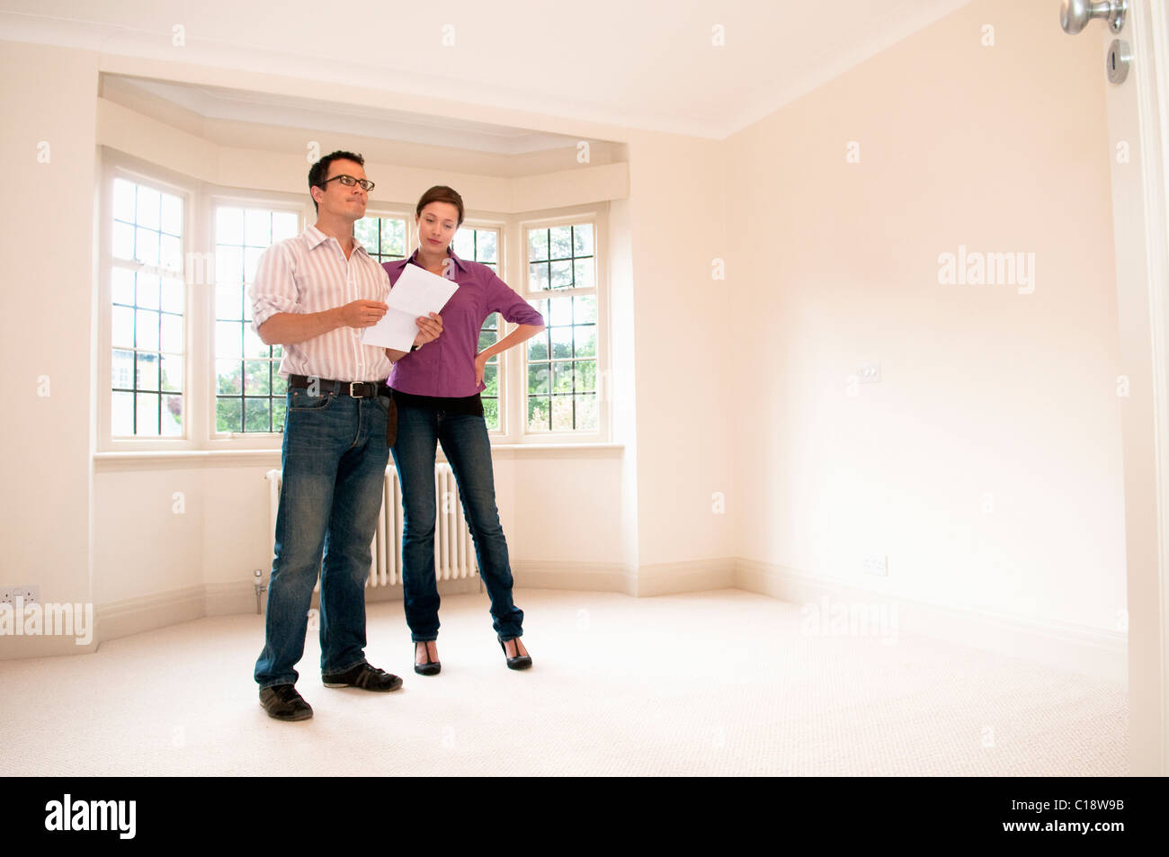 Couple look at room in vacant house - Stock Image
