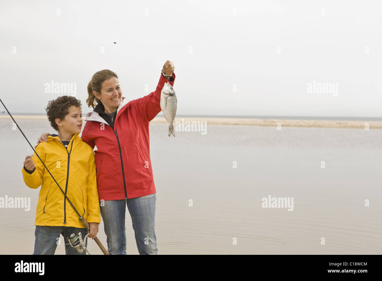 Mother and son looking proudly at fish - Stock Image