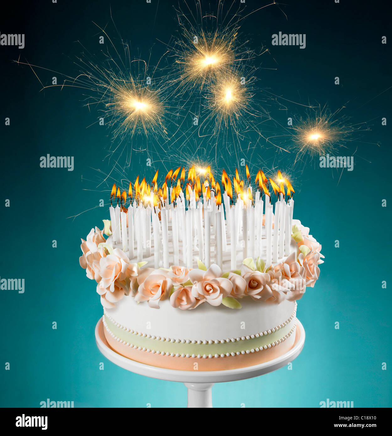 Birthday cake with lots of burning candles - Stock Image