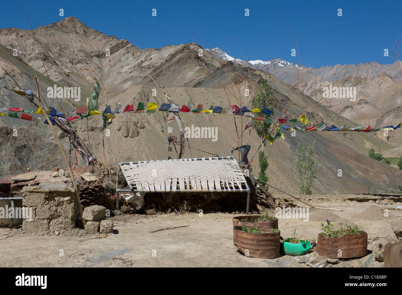Old charpoy bed and prayer flags on a rooftop, Lamayuru Gompa, Lamayuru, (Ladakh) Jammu & Kashmir, India - Stock Image