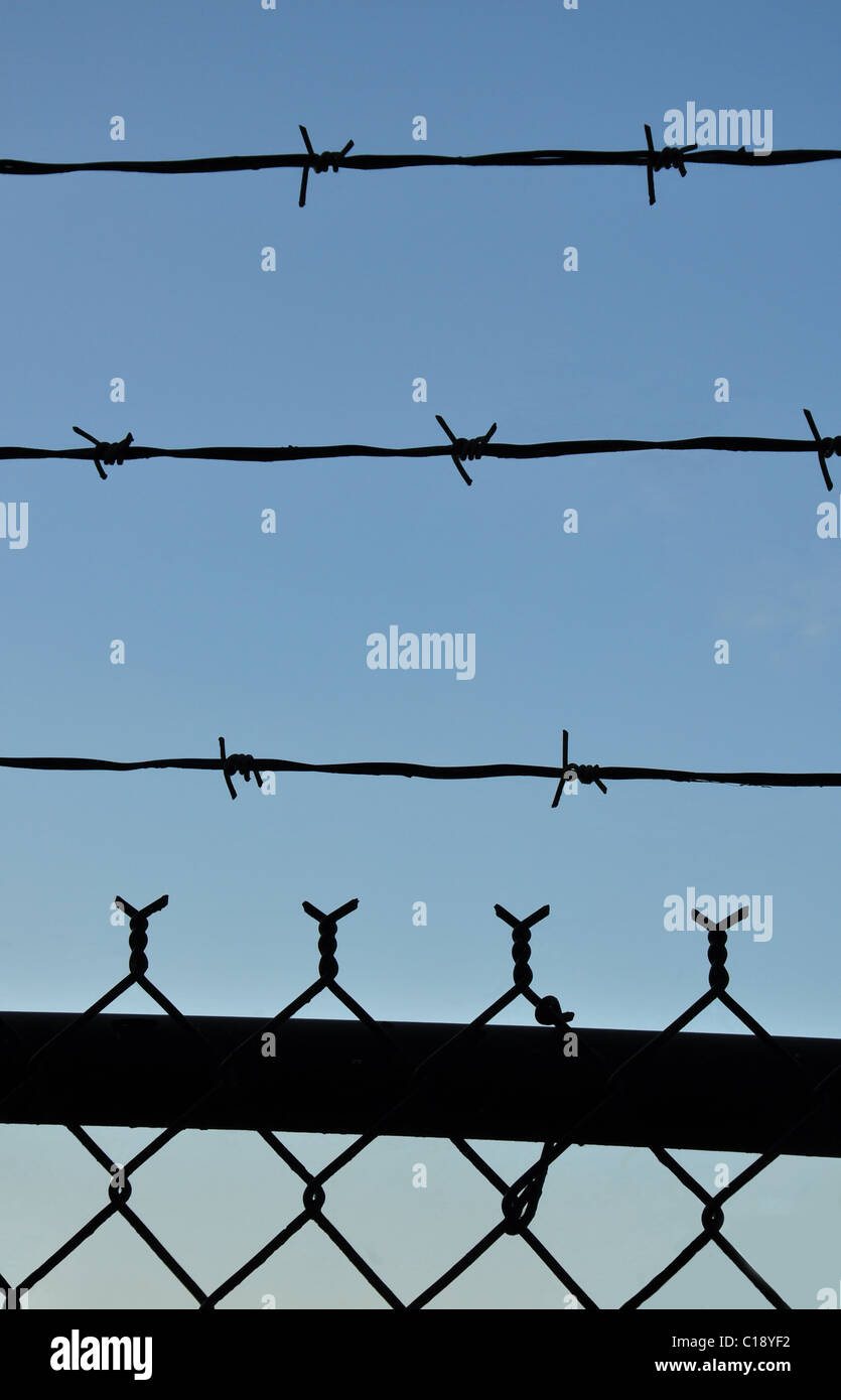Barbed wire and fence against a bright blue sky - Stock Image