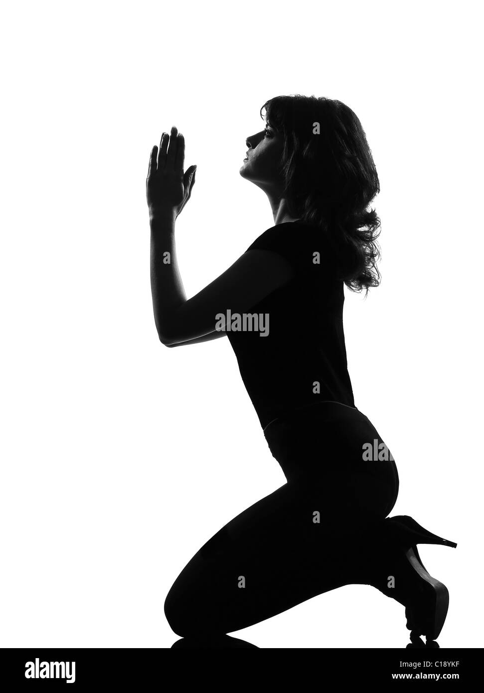 full length silhouette in shadow of a young woman kneel pray implore  in studio on white background isolated - Stock Image