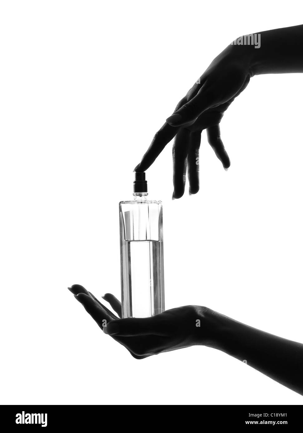 detail close-up silhouette in shadow of a  woman hands holding perfume in studio on white background isolated Stock Photo