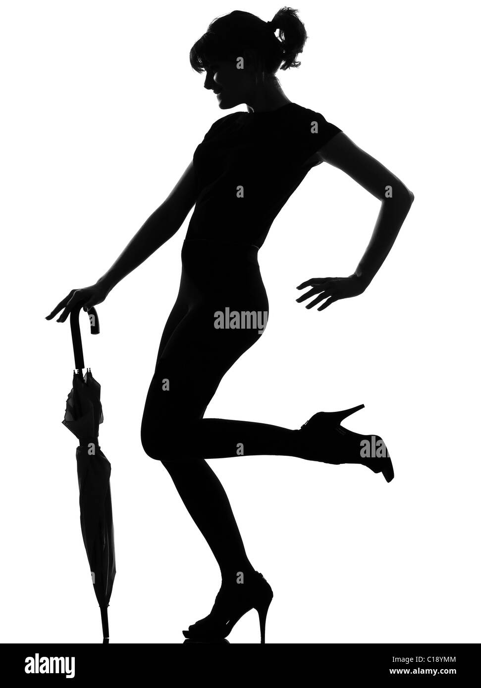 full length silhouette in shadow of a young woman with closed umbrella  in studio on white background isolated - Stock Image