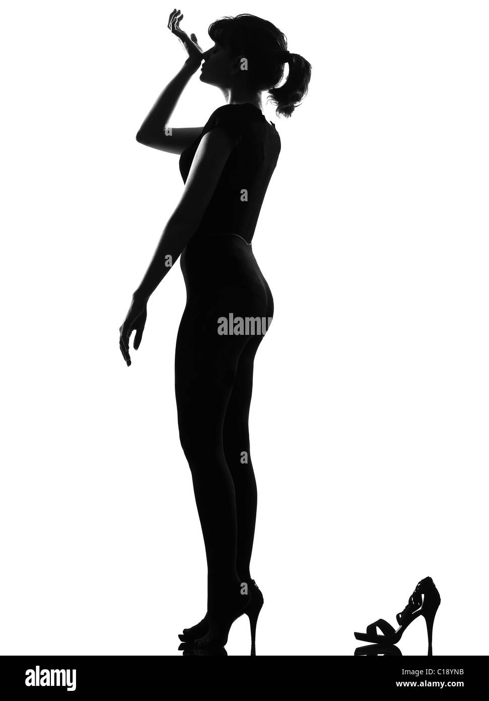 silhouette in shadow of a young woman smelling perfume  in studio on white background isolated - Stock Image