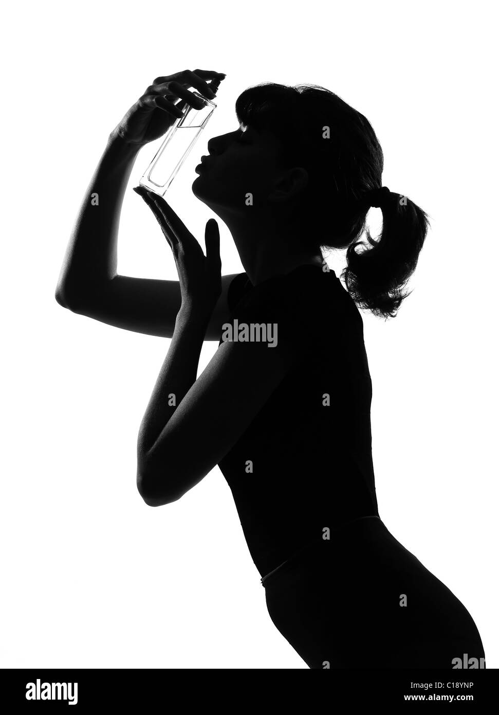 silhouette in shadow of a young woman kissing her perfume bottle  in studio on white background isolated - Stock Image