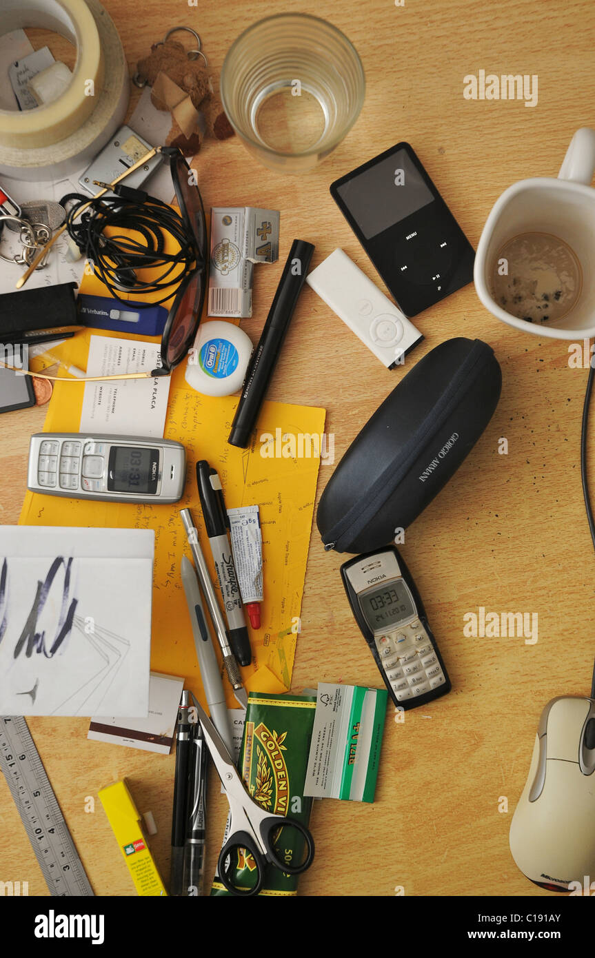 A perpendicular view of a messy desk surface with all sorts of stationary, electronics and dirty mugs. - Stock Image