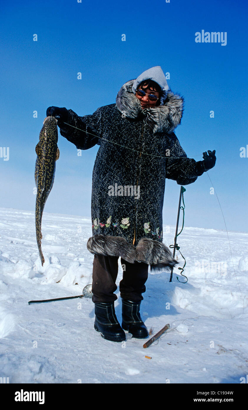 Inuit woman with a caught migratory Artic Char, Nuiqsut, on the coast of the Arctic Ocean in the far north of Alaska Stock Photo