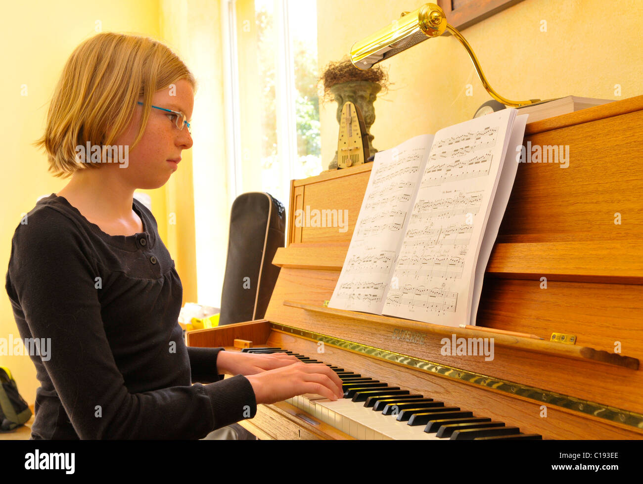 Girl playing the piano - Stock Image