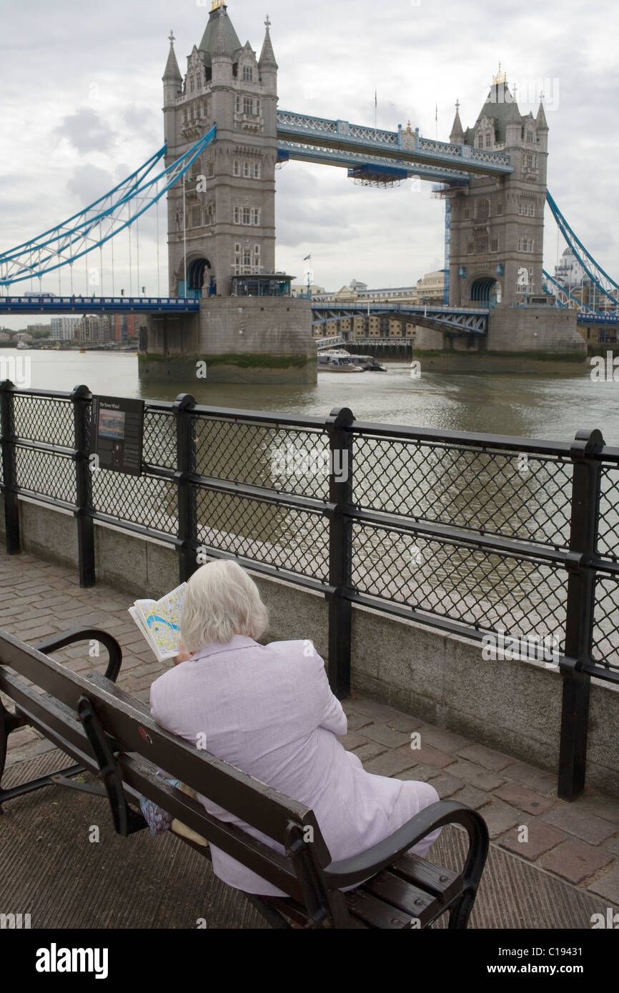A white haired woman looks at a London A-Z map sat near Tower Bridge on the river Thames. Stock Photo