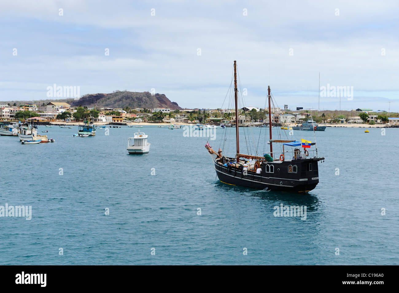 Harbour of San Cristóbal Island on Galapagos with an ancient sailing boat in the front, Ecuador, South America - Stock Image