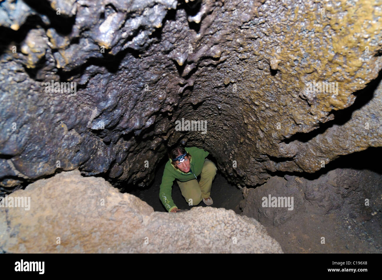 Lava River Cave, cave explorer wearing a headlamp in a volcanic lava tube, Newberry National Volcanic Monument - Stock Image