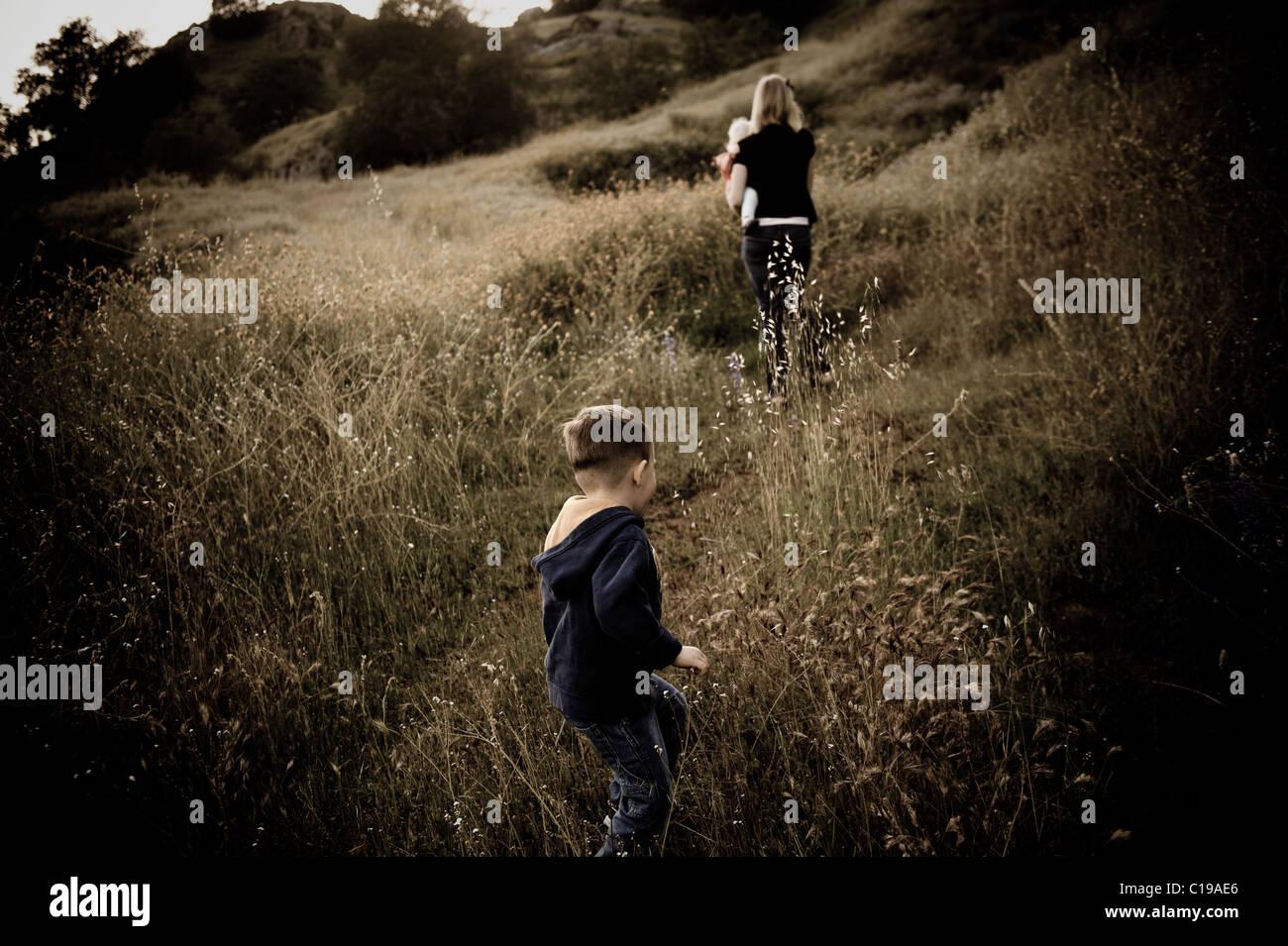 A little boy follows his mother through tell grass. - Stock Image
