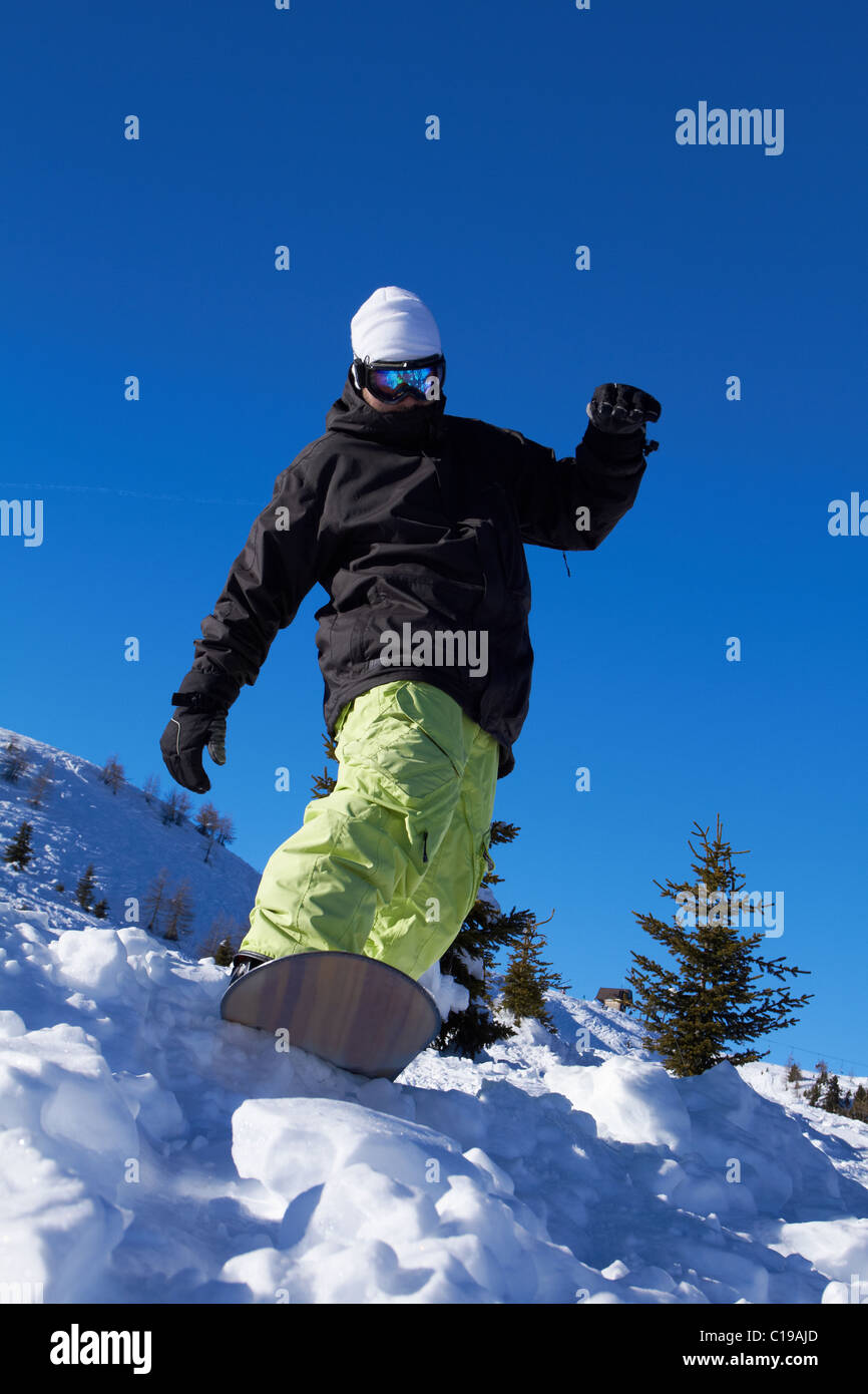 Sporty snowboarder riding on snow in high mountains Stock Photo