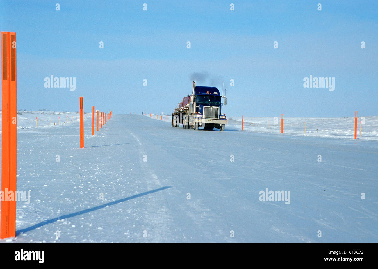Truck driving on an ice road, built by oil companies and used to connect individual oil drilling sites in winter, - Stock Image