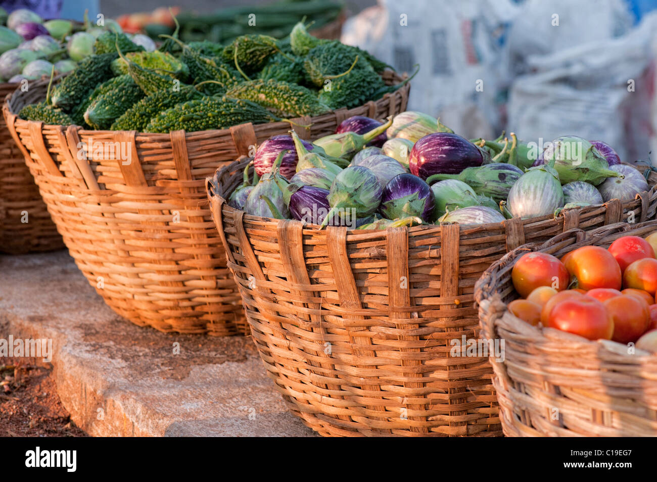 Aubergines / Eggplant , Tomatoes and Bitter gourd in baskets at an Indian market. Andhra Pradesh, India - Stock Image