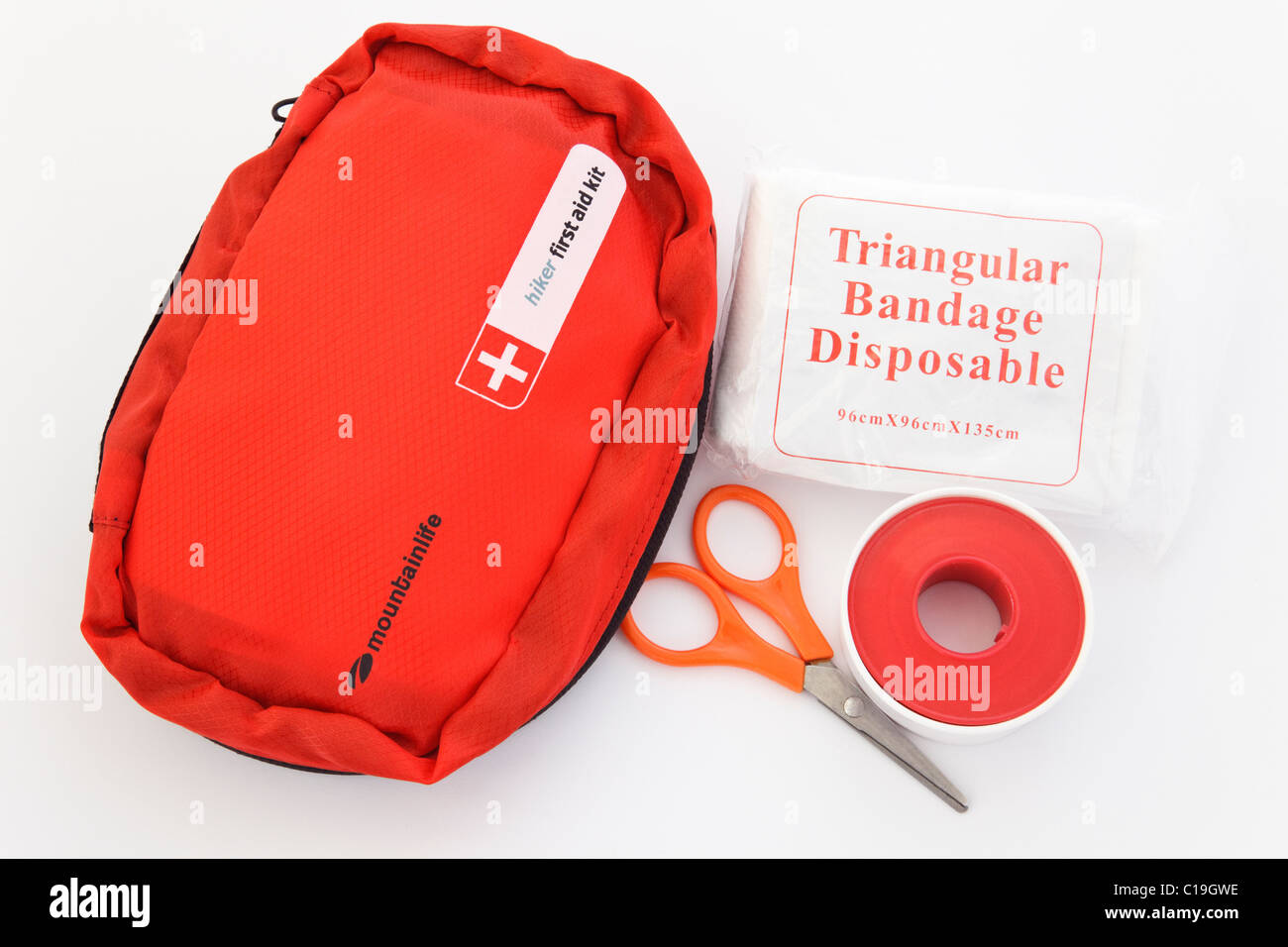 Hiker's first aid kit in a red bag with a triangular bandage packet, tape and scissors. England UK - Stock Image