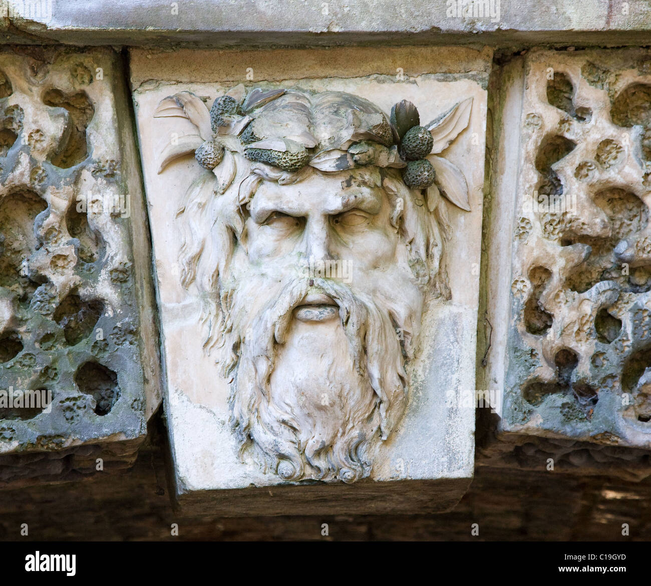 Druids head forming the keystone of an arched bridge in Croome Park in Worcestershire - Stock Image