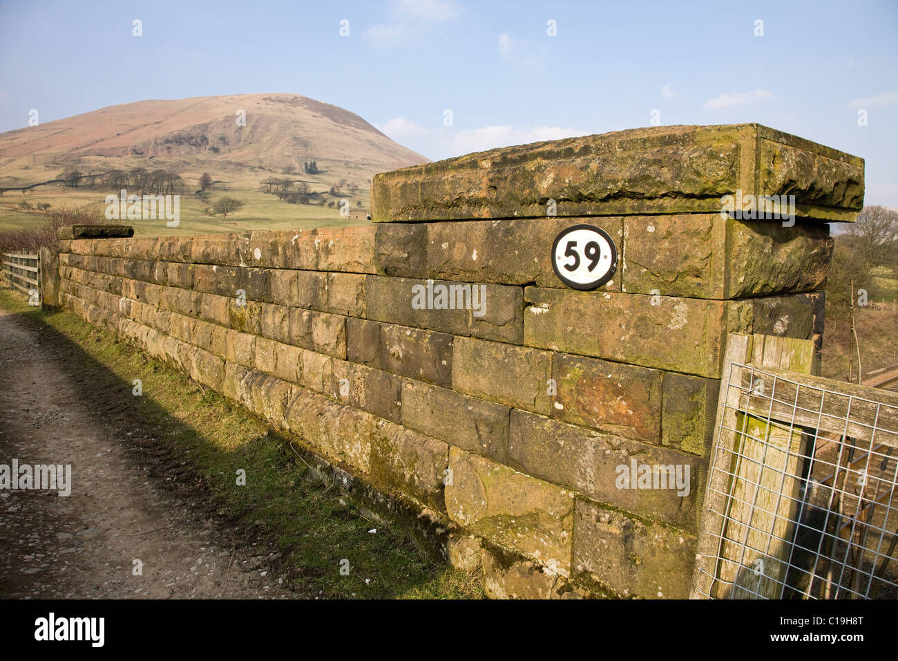 Bridge number fifty nine on the Sheffield to Manchester train line in Edale with Grindslow Knoll on Kinder Scout - Stock Image