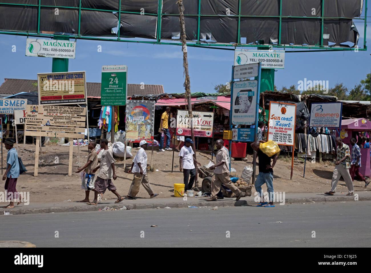 Africans walking past advertising bill boards hoardings in casual street scene Mombasa Kenya - Stock Image