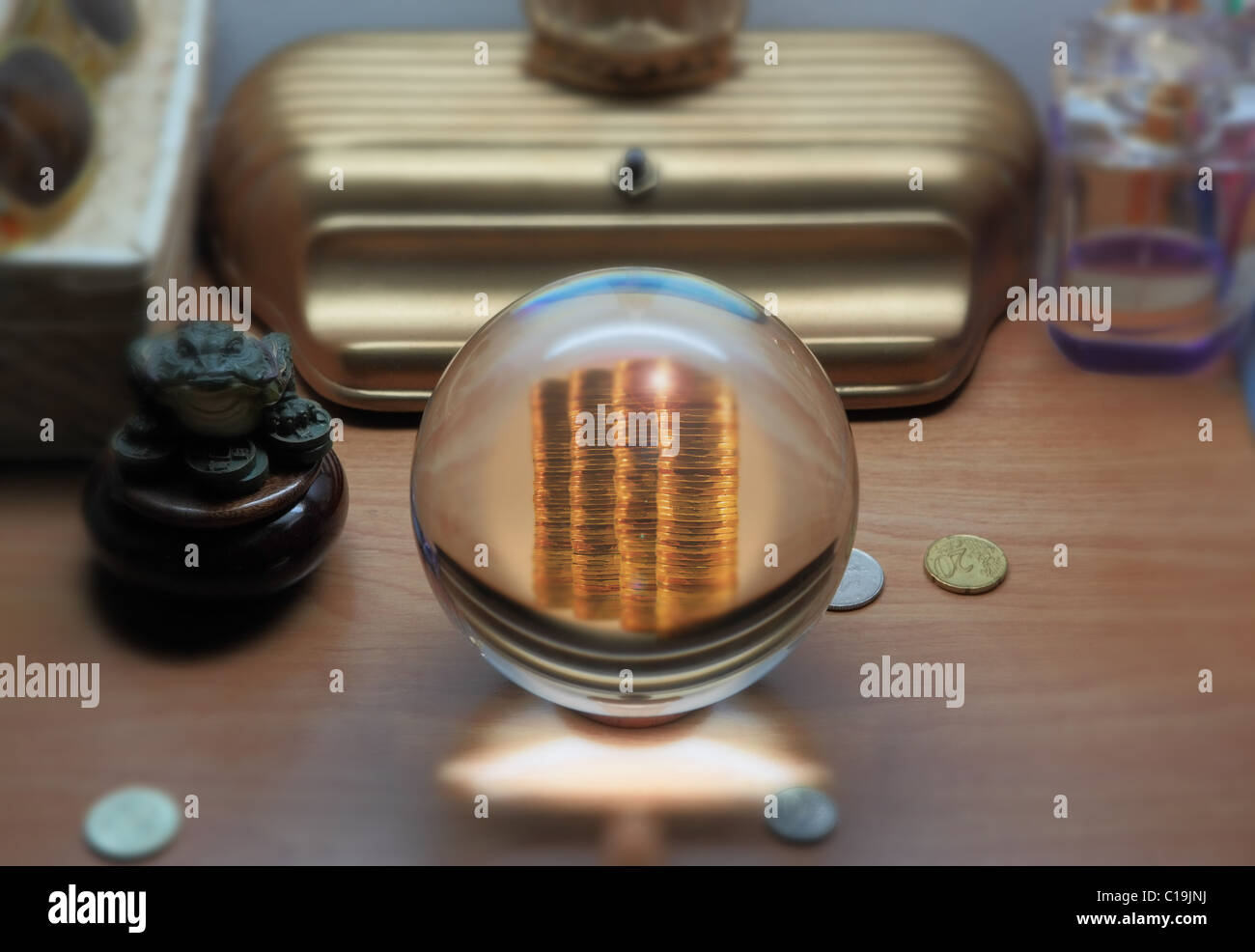 stack of coins seen in crystal ball, coins and various objects are also seen on table - Stock Image