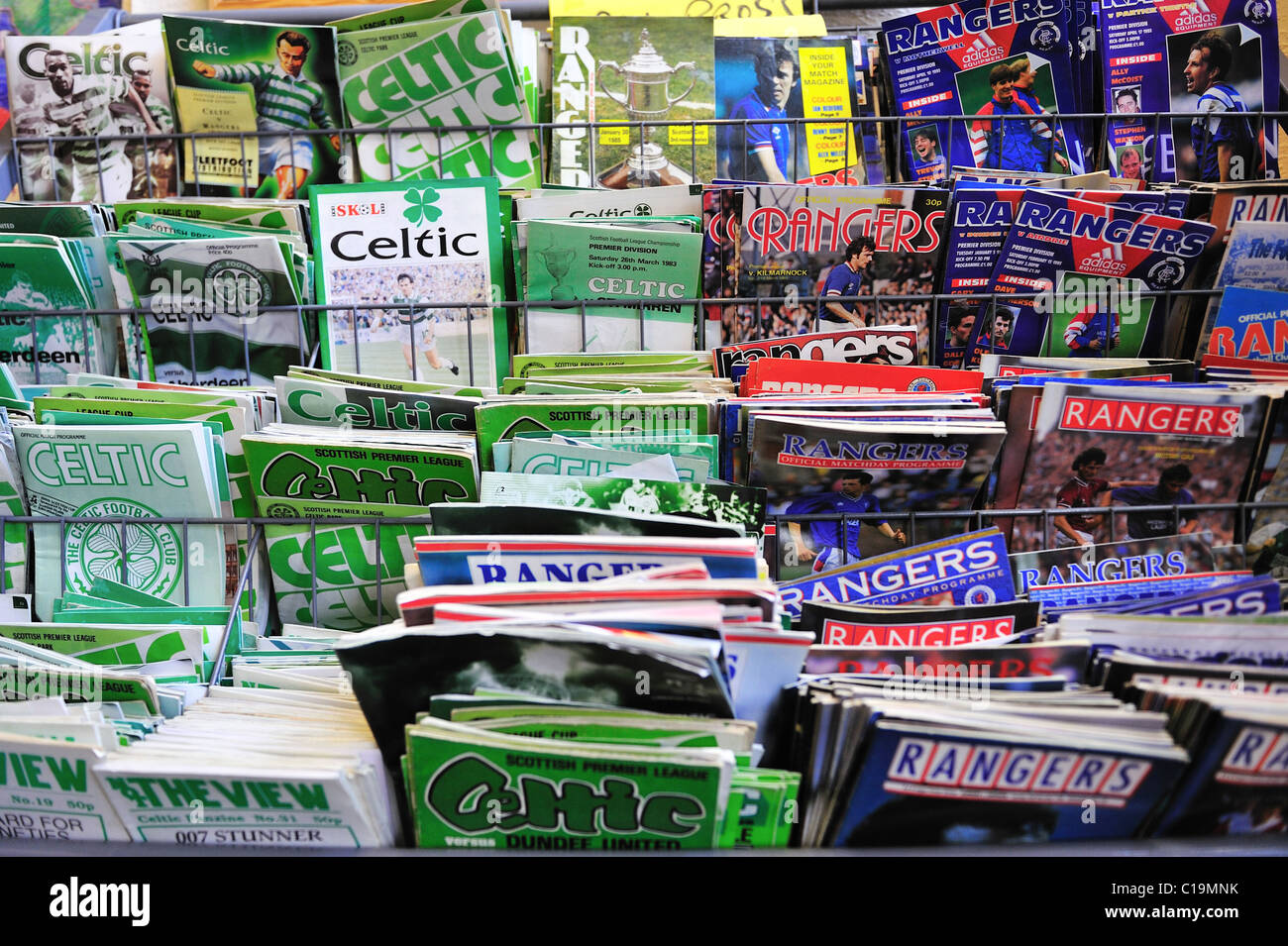 Programmes of Glasgow's famous football rivals, Celtic and Rangers, living cheek-by-jowl in perfect disharmony - Stock Image