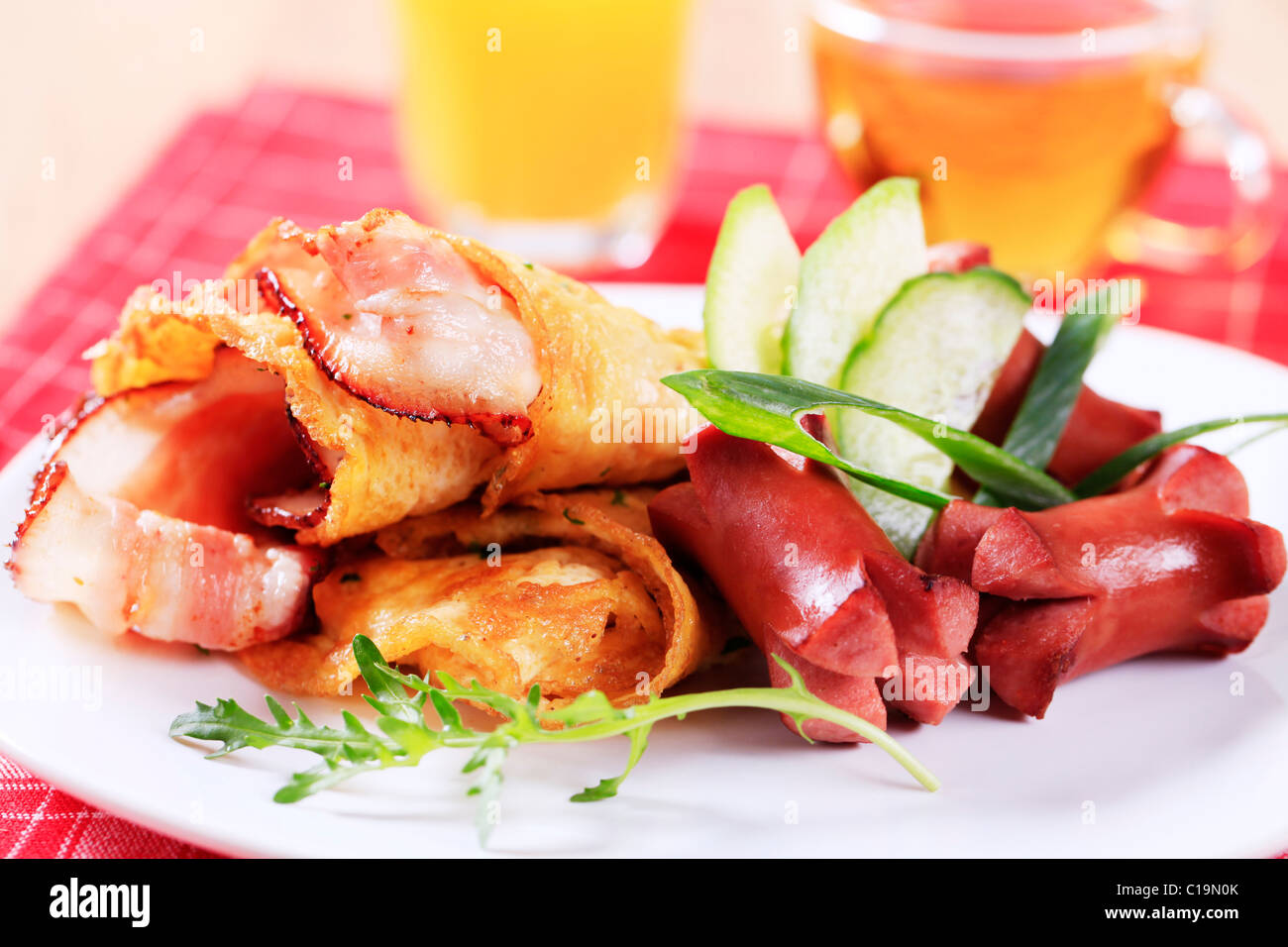 Fried egg omelet with bacon and sausages - Stock Image