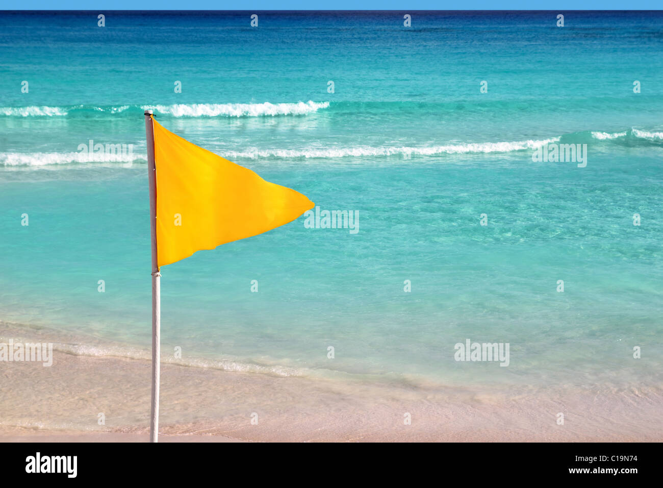 beautiful beach yellow flag weather indication signal - Stock Image