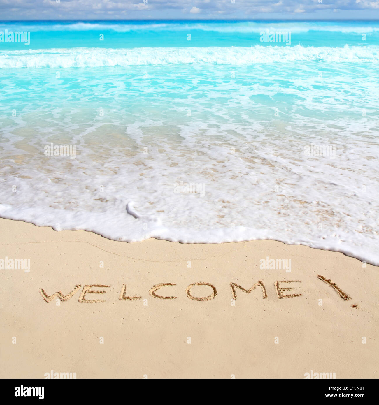 greetings welcome beach spell written on sand Caribbean tropical sea - Stock Image